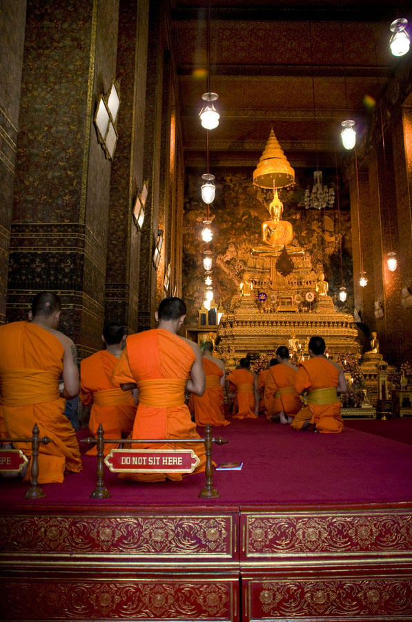 Wat Pho temple. Praying in front of Buddha golden statue