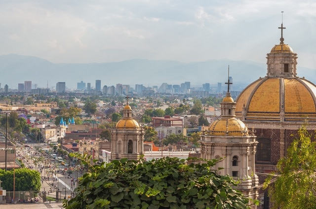 Old basilica of guadalupe with mexico city skyline behind it