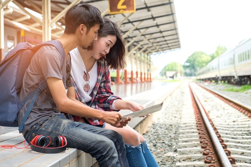 Asian male and female tourists planning a train trip.