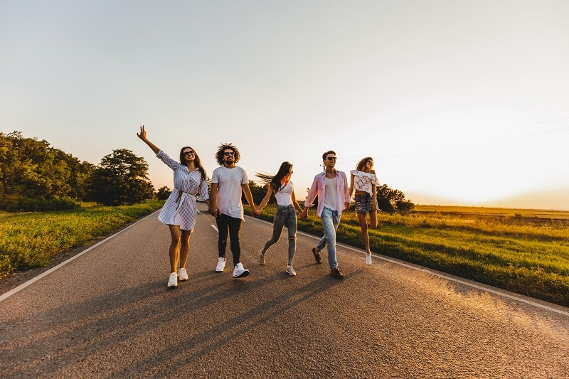 Company of happy young stylish guys walk on a country road on a sunny day