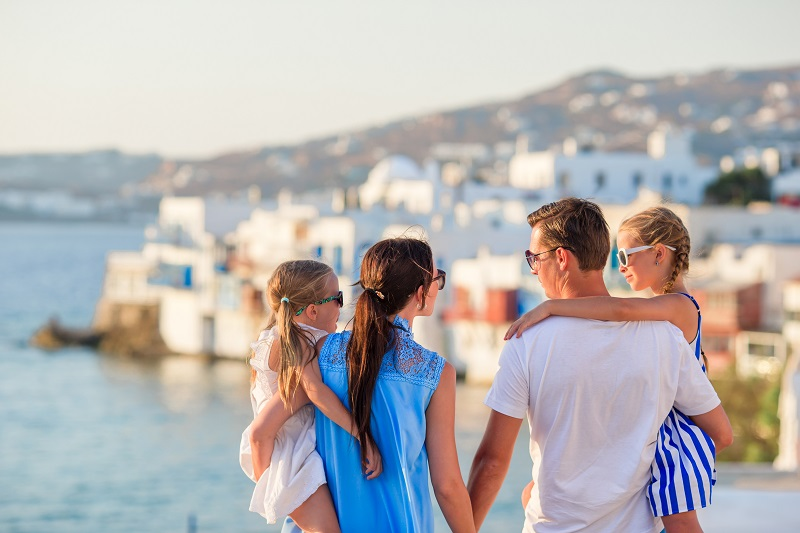 Family vacation in Europe. Parents and kids on Little Venice background on Mykonos Island, in Greece