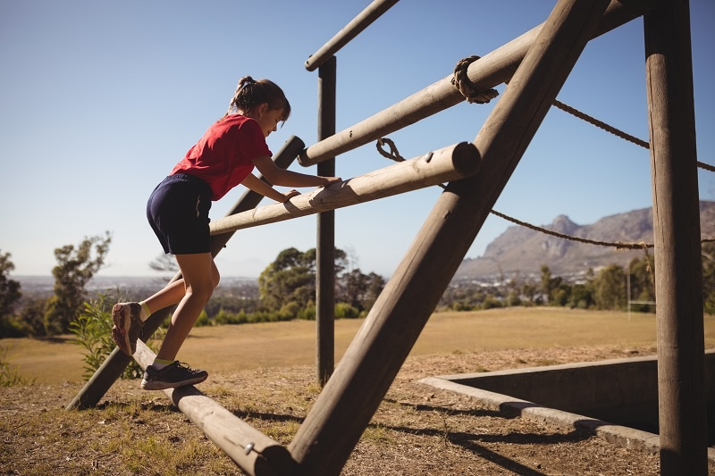 Girl exercising on outdoor equipment during obstacle course in training camp