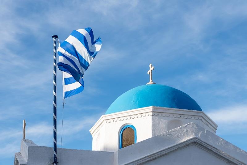 Greek flag and orthodox church in Mykonos, Greece