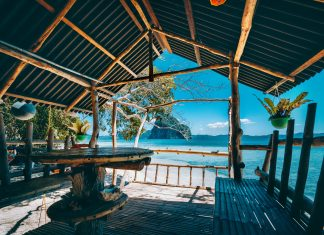 Tropical getaway remote panorama of impressive Pinagbuyutan island from the native wood and bamboo terrace, beauty of Philippines island