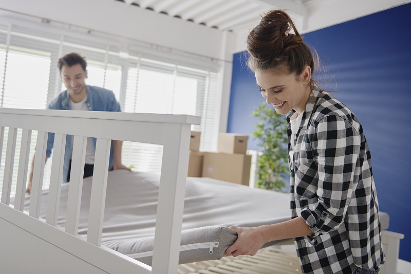 Couple putting mattress on the bed