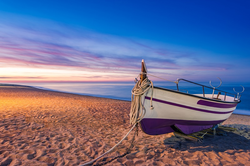 Old wooden fishing boat on beach at sunrise
