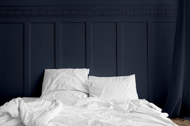 White bed linen on a mattress in a midnight blue bedroom