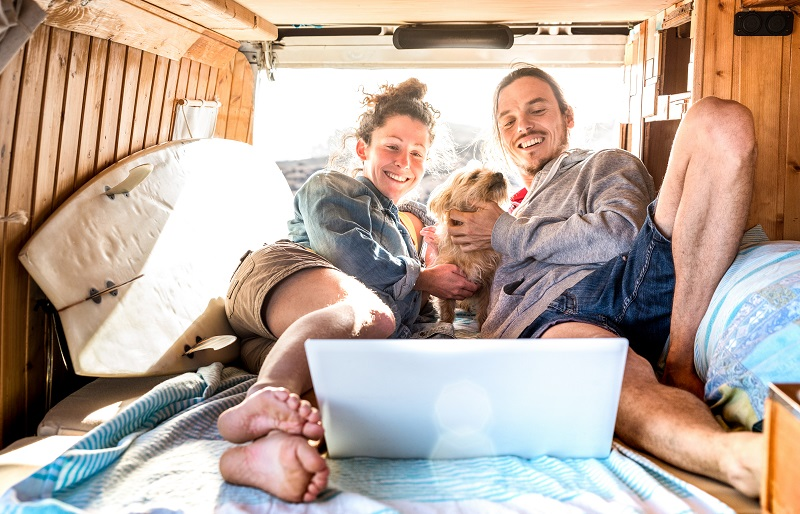 Digital nomad couple with cute dog using laptop on retro mini va