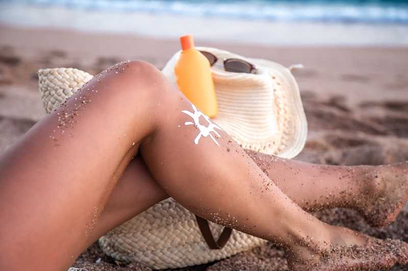 Sunscreen on a woman's feet on the beach.