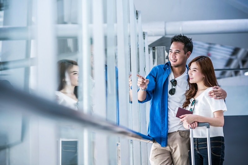 Asian couple traveler holding the passport with suitcases at the