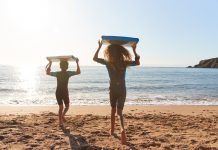 Rear View Of Children In Wetsuits Carrying Bodyboards On Summer Beach Vacation Having Fun By Sea