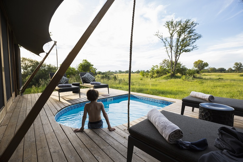 Botswana,A boy in a swimming pool at a safari camp, looking out over the landscape