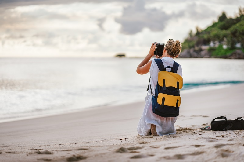 Travel tourist female photograph sunset at tropical beach. Recreation hobby summer vacation lifestyle concept