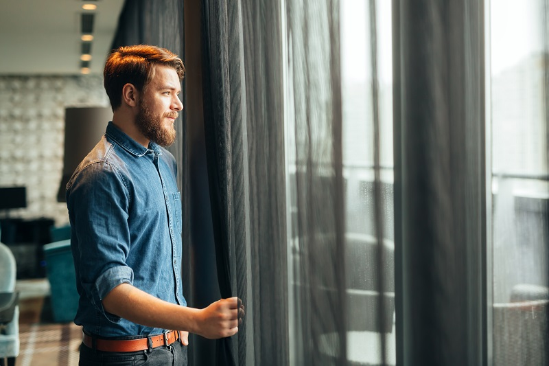 Man enjoying view from luxurious hotel room