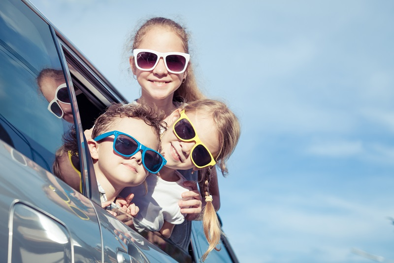 Happy children getting ready for road trip on a sunny day