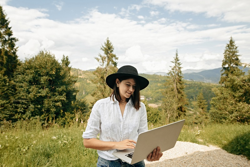 Hipster girl with laptop sitting on wooden porch